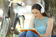 Student memorizing and listening tutorial. Concentrated student memorizing notes and listening an audio tutorial with headphones in a park Stock Image