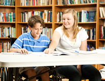 Student Mentoring Program. Teenage girl mentoring a younger, disabled boy in the school library royalty free stock images