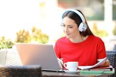 Student met hoofdtelefoons e-leert met laptop stock afbeeldingen
