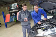 Student met instructeur die auto herstelt tijdens leertijd royalty-vrije stock fotografie