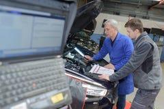 Student met instructeur die auto herstelt tijdens leertijd stock afbeelding