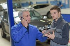 Student met instructeur die auto herstelt tijdens leertijd royalty-vrije stock foto's