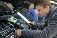 Student met instructeur die auto herstelt tijdens leertijd royalty-vrije stock foto