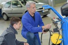 Student met instructeur die auto herstelt tijdens leertijd stock afbeeldingen