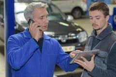 Student met instructeur die auto herstelt tijdens leertijd stock foto's