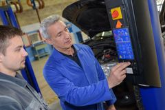 Student met instructeur die auto herstelt tijdens leertijd royalty-vrije stock afbeelding