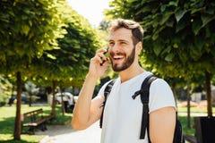 Student met rugzak die bij cellphone spreekt royalty-vrije stock foto's
