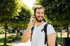 Student met rugzak die bij cellphone spreekt stock afbeeldingen