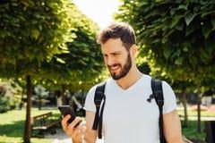 Student met rugzak die bij cellphone spreekt stock fotografie