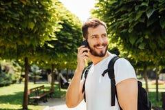 Student met rugzak die bij cellphone spreekt stock afbeelding