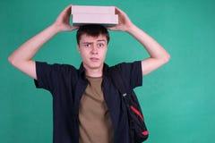 Student met zware boeken op zijn hoofd Royalty-vrije Stock Foto's