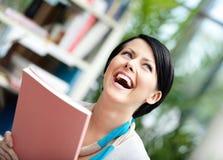 Student mit Buch an der Bibliothek lizenzfreie stockbilder