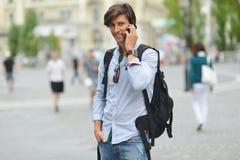 Student mit dem beweglichen intelligenten Telefongehen Stockfoto