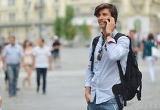 Student mit dem beweglichen intelligenten Telefongehen Lizenzfreie Stockbilder