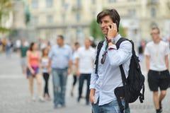 Student mit dem beweglichen intelligenten Telefongehen Lizenzfreies Stockfoto