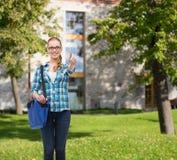 Student mit der Laptoptasche, die sich Daumen zeigt Stockfotos