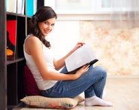 Student mit einem lbook in einer Bibliothek Stockfoto