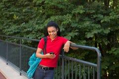 Student mit einem Rucksack, der ihren Handy betrachtet Stockfotos