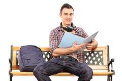 Student mit Kopfhörern ein Buch lesend Lizenzfreie Stockfotos