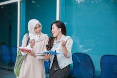 Student mit zwei Asiaten, der auf dem Campus studiert Lizenzfreies Stockbild