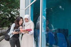 Student mit zwei Asiaten, der auf dem Campus studiert Lizenzfreies Stockfoto
