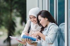 Student mit zwei Asiaten, der auf dem Campus studiert Lizenzfreie Stockbilder