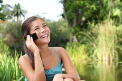 Student on mobile phone. Student talking on mobile phone outdoors in a park on university campus. Cute young woman model Stock Photo
