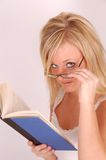 Student Model. Young blonde woman with glasses reading book and looks at camera royalty free stock photography