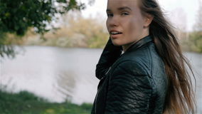 Student Model Looks Around, smiling and make some flirt.Camera Follows Behind Teen Girl Walking Through City Park. stock video