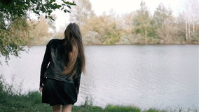 Student Model Looks Around, smiling and make some flirt.Camera Follows Behind Teen Girl Walking Through City Park. stock footage