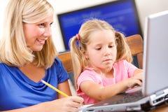 Student: Moderportionflickan gör läxa på bärbara datorn Arkivfoto