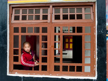 Student Monk. A child Buddhist student peeping from a window of the Ralang Monastery, Sikkim, India Royalty Free Stock Photos