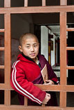 Student Monk. A child Buddhist student peeping from a window of the Ralang Monastery, Sikkim, India Stock Photography
