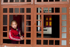 Student Monk. A child Buddhist student peeping from a window of the Ralang Monastery, Sikkim, India Royalty Free Stock Image