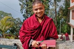 Student Monk at Do Drul Chorten Stupa. A Buddhist monk holding a copy of Buddhist manuscript in hand at Do Drul Chorten Stupa at Sikkim, India Stock Image