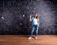 Student mot en stor svart tavla med matematiska symboler Arkivbilder