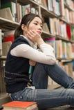 Student nahe bei dem Bücherregal, das niedergedrückt schaut Lizenzfreie Stockfotos