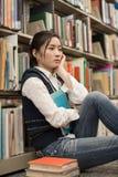 Student nahe bei dem Bücherregal, das niedergedrückt schaut Stockfoto