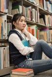Student nahe bei dem Bücherregal, das niedergedrückt schaut Stockbilder