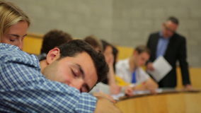 Student napping in the lecture hall and then waking up stock footage