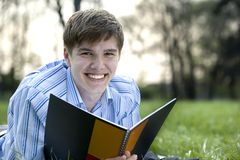 Student in nature. Attractive man lying on grass while holding a notebook in his hands Stock Image