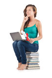 Student with netbook. Sitting on books Stock Image