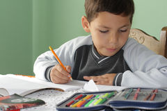 Student notebooks and pens. Little boy at the table for homework Stock Image