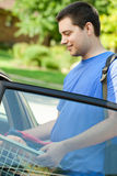 Student off to college. A young man college student with backpack putting laundry in the car to go back to school Royalty Free Stock Image