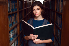Student with open book in college library. Stock Photos