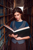 Student with open book  in college library. Royalty Free Stock Images