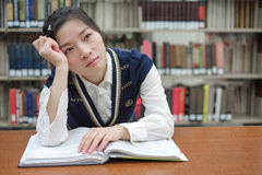 Student with open textbook deep in thought Stock Photos