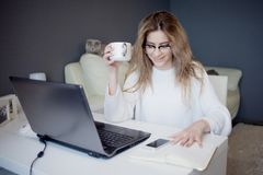 Student Or Freelancer, Working At Home With Laptop. Charming Young Woman Sits In Front Of Monitor With Cup Of Coffee. Stock Photos