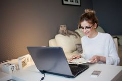 Student Or Freelancer, Working At Home With Laptop. Charming Young Woman Sits In Front Of The Monitor A With Notepad Stock Photo