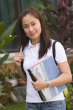 Student outdoor. Smiling student carrying bag and books outdoors royalty free stock photo